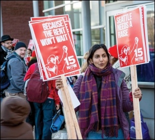 Socialist Seattle councillor hands out '$15 now' placards, photo Socialist Alternative