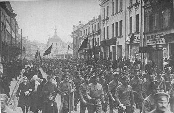 Bolshevik regiments marching to Smolny under banners emblazoned with All Power to the Soviets, Long Live the Revolution.