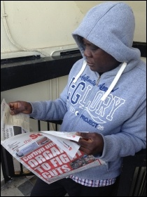 Resident reads the Socialist while defending the blocks, photo by Paula Mitchell