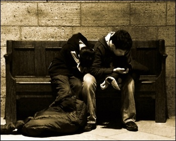 Young woman and man wait on a bench with a sleeping bag at night, photo Tony Fischer (Creative Commons)