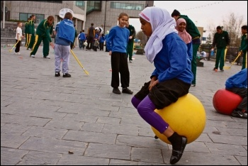Primary school children playing outside on space hoppers, photo National Assembly for Wales (Creative Commons)
