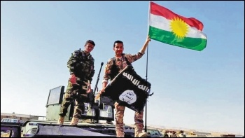 US-backed Kurdish Peshmerga forces replace the Isis flag following territorial gains, photo Creative Commons