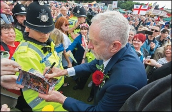 Jeremy Corbyn signing an autograph for a supporter - his policies are rightly popular, but if he wins, he will face opposition from the billionaire class, the Blairites and the state, photo by Paul Mattsson