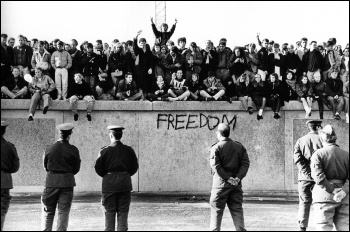 Students atop of the Wall at the Brandenburg gate during the dying days of the East German regime