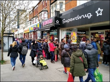 A queue out the door of a pharmacy in East Ham, London, March 2020, photo by Dave Carr